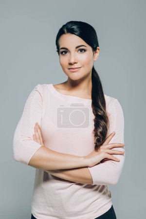 portrait attractive brunette woman with arms crossed posing isolated on grey