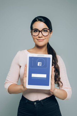 woman in eyeglasses showing digital tablet with facebook appliance, isolated on grey