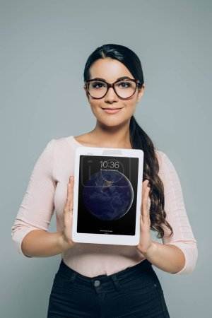 Photo for Attractive woman in eyeglasses showing ipad tablet, isolated on grey - Royalty Free Image