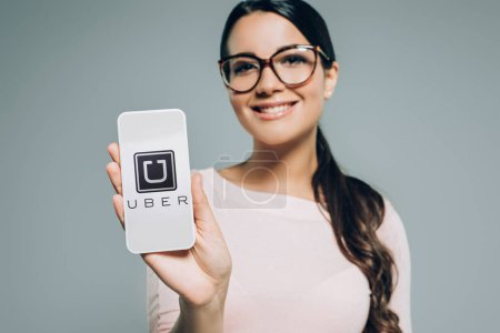 Photo for Attractive girl showing smartphone with uber appliance, isolated on grey - Royalty Free Image