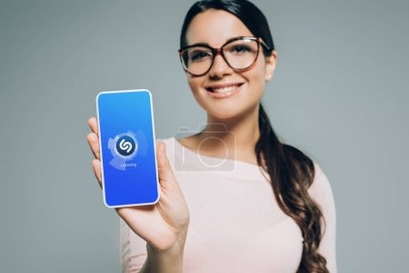 Photo for Smiling girl showing smartphone with shazam app, isolated on grey - Royalty Free Image