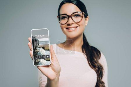 Photo pour Femme montrant smartphone avec application pour billets, isolé sur gris - image libre de droit