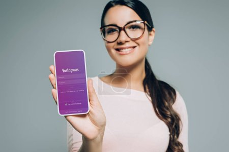Photo for Smiling girl presenting smartphone with instagram appliance, isolated on grey - Royalty Free Image