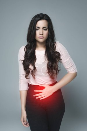 beautiful girl suffering from abdominal pain with red painful point, isolated on grey