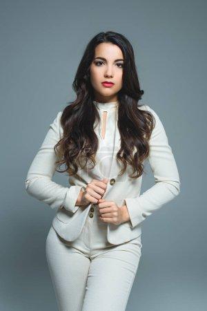 Photo pour Belle femme élégante en costume blanc, isolée sur gris - image libre de droit