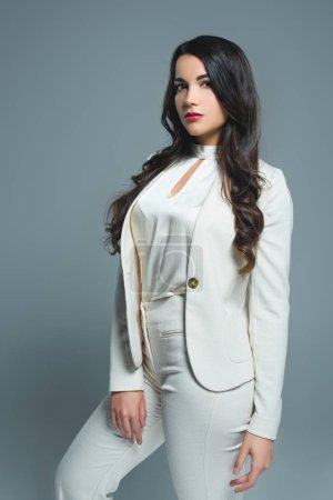 Photo pour Belle fille posant en costume blanc tendance, isolé sur gris - image libre de droit