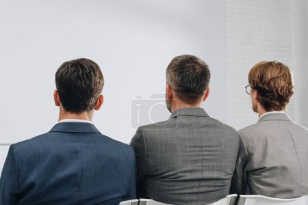 rear view of three businessmen sitting on chairs during training in hub
