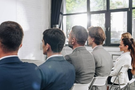 rear view of businesspeople sitting on chairs during training in hub