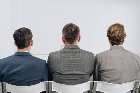 back view of three businessmen sitting on chairs during training in hub