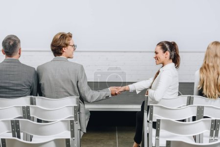 side view of businessman and businesswoman shaking hands during business training in hub