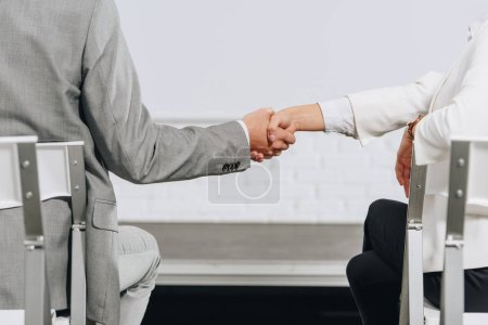 cropped image of businessman and businesswoman shaking hands during business training in hub