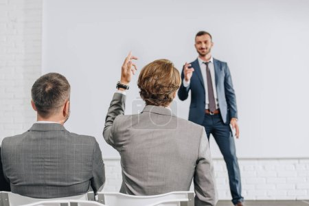 back view of businessman rising hand to coach during training in hub