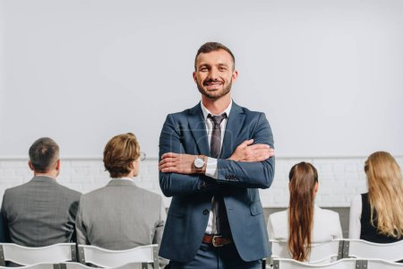smiling coach with crossed arms looking at camera during business training in hub