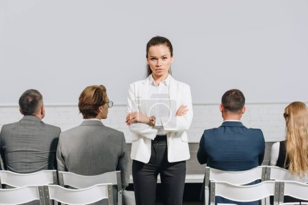 serious coach with crossed arms looking at camera during business training in hub