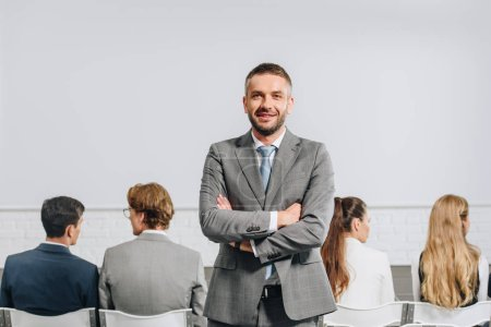 handsome coach with crossed arms looking at camera during business training in hub