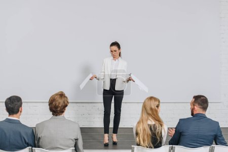 Photo for Beautiful business coach standing on stage and gesturing during training in hub - Royalty Free Image