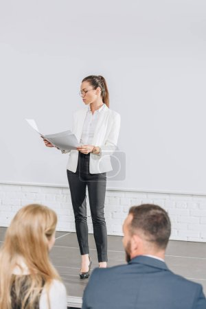 Photo for Attractive business coach standing on stage and looking at documents during training in hub - Royalty Free Image