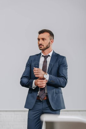 handsome businessman buttoning sleeve in hub