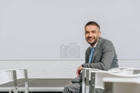 handsome smiling businessman sitting on chair in hub