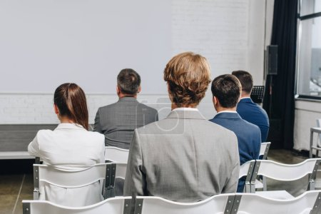 back view of businesspeople sitting on chairs at training in hub