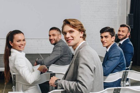 smiling businesspeople sitting on chairs at training in hub and looking at camera