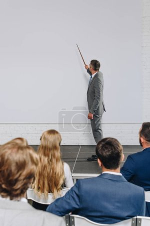 handsome business coach pointing on board with pointer stick during training in hub