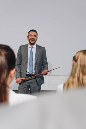 laughing handsome business coach holding pointer stick during training in hub