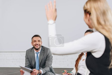 handsome business coach looking at participant with raised hand during training in hub