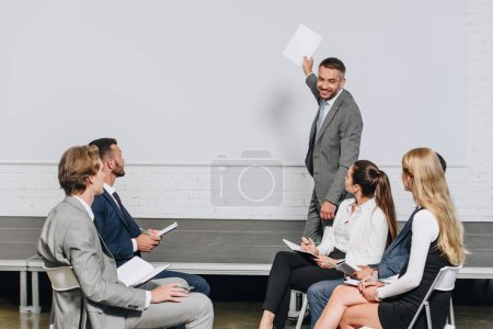smiling business coach pointing on board during training in hub