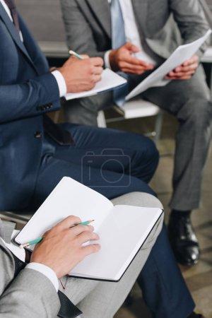 Photo pour Cropped image d'hommes d'affaires, écrire quelque chose aux ordinateurs portables au cours de la formation dans le moyeu - image libre de droit