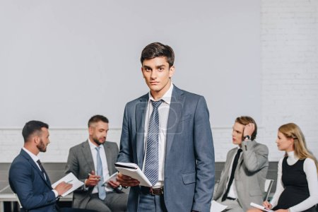 handsome business coach standing in front of businesspeople at training in hub
