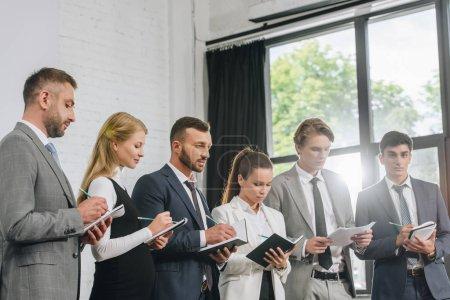 Photo pour Businesspeople, debout dans la rangée et écrire quelque chose aux ordinateurs portables au cours de la formation dans le moyeu - image libre de droit