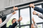 low angle view of businesspeople showing thumbs up in hub