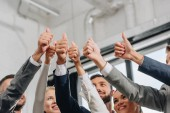 low angle view of smiling businesspeople showing thumbs up in hub
