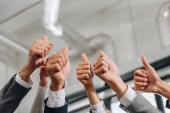 cropped image of businesspeople showing thumbs up in hub