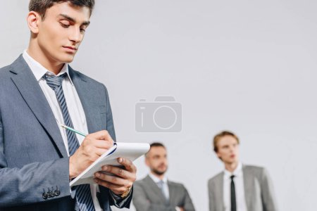 handsome businessman writing something to notebook with pencil in hub