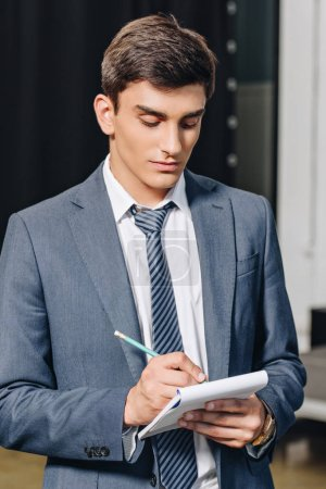 handsome businessman writing something to notebook in hub