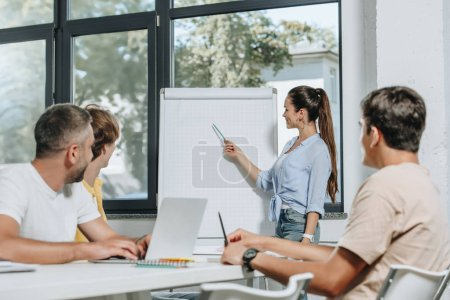 businesswoman presenting project to colleagues at meeting in office