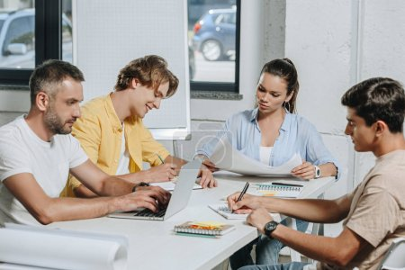 businesspeople sitting at table during meeting in light office
