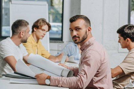 Photo pour Bel homme d'affaires, regardant la caméra au cours de la réunion dans le Bureau - image libre de droit