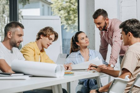 businessmen and businesswoman sitting at table during meeting in office
