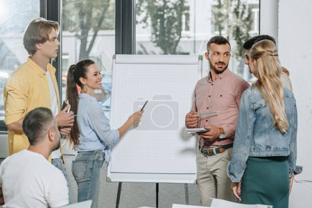 young businesspeople standing near flipchart in office