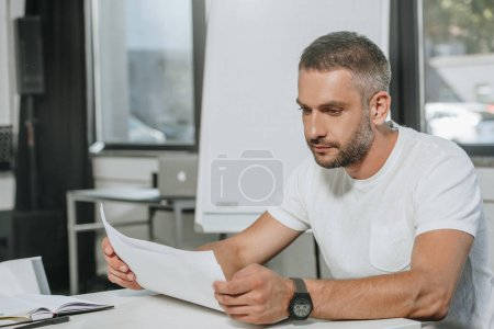 Photo for Handsome businessman reading documents in office - Royalty Free Image