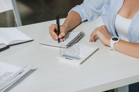 cropped image of businesswoman writing something to notebook at table in office