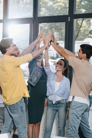 businesspeople celebrating success and giving high five in office
