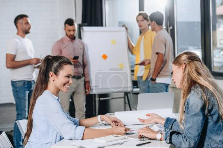 smiling businesswomen looking at documents during meeting in office