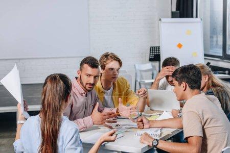 Unzufriedene Geschäftsleute sitzen bei Treffen im Amt mit am Tisch