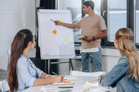 businessman pointing on flipchart during presentation in office