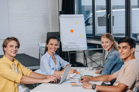 smiling team of businesspeople looking at camera during meeting in office