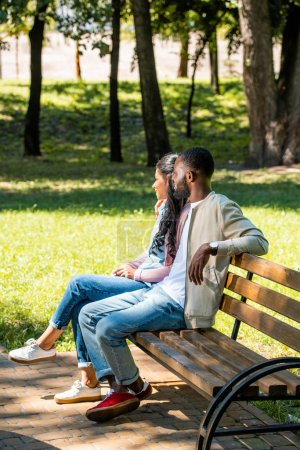 african american couple sitting on wooden bench in park and looking away